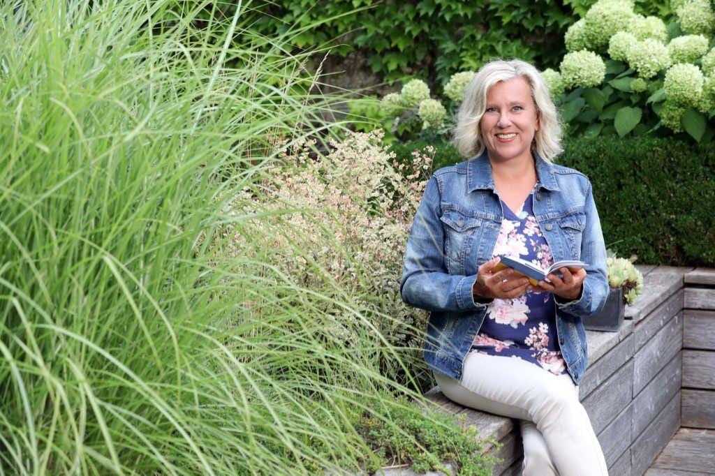 Pressefoto Mag. Brigitte Zadrobilek sitzend im Garten mit Buch